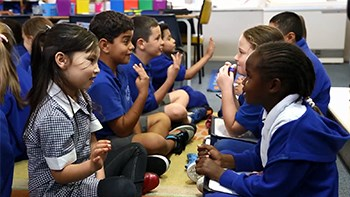 Students facing each other as they sit on the floor in two rows. Students in each pair looking at each other and talking, with some counting on their fingers.